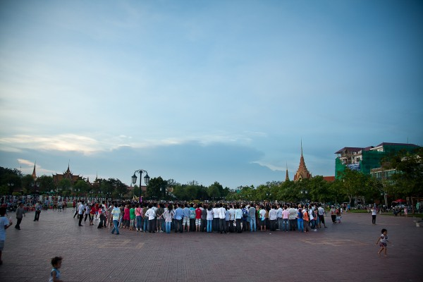 People crowd around a street performance in Phnom Penh