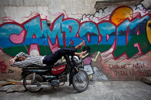 A motorcycle taxi driver naps in front of Graffiti, Phnom Penh